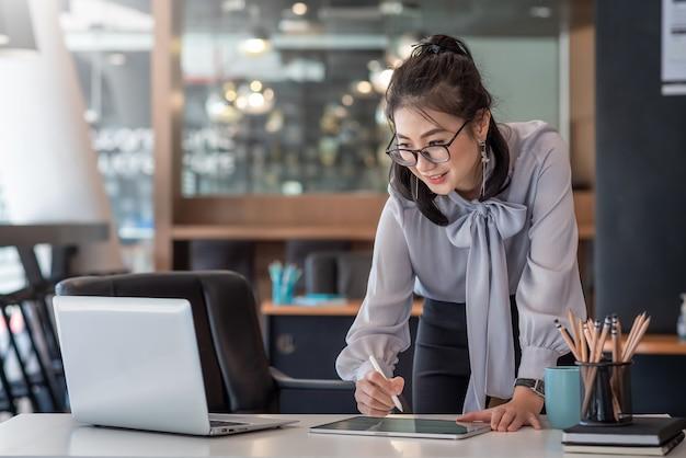 Donna di affari asiatica che lavora su un tablet guardando lo schermo del laptop in ufficio.