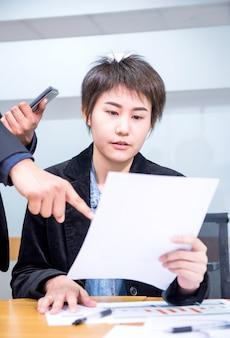 Le donne d'affari asiatiche stanno lavorando con un collega in ufficio