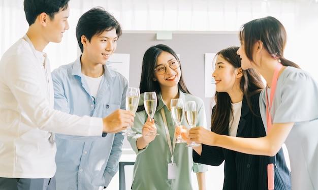 Le persone d'affari asiatiche brindano ai loro bicchieri per celebrare i risultati