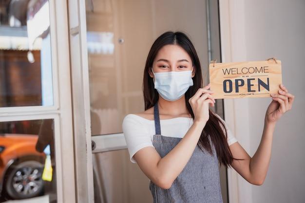Proprietario di un negozio di caffè asiatico che indossa una maschera, donna con cartello per aprire dopo la chiusura della città