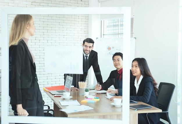L'uomo e la donna di affari asiatici e caucasici guardano la donna caucasica del responsabile che dà la presentazione al posto di lavoro.