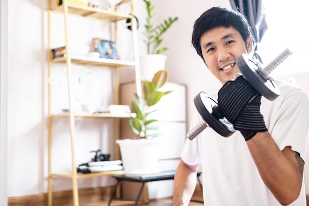 L'uomo caucasico asiatico tiene il manubrio in casa