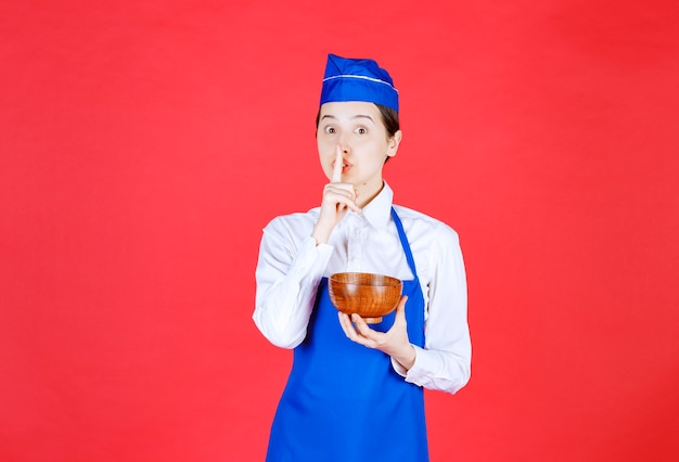 Chef asiatico in grembiule blu che tiene una ciotola di ceramica di tè verde o tagliatelle e chiede silenzio.