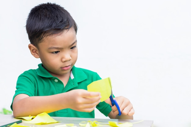 Pratica asiatica del ragazzo del bambino al taglio della carta di colore dalle forbici sulla tavola di legno.
