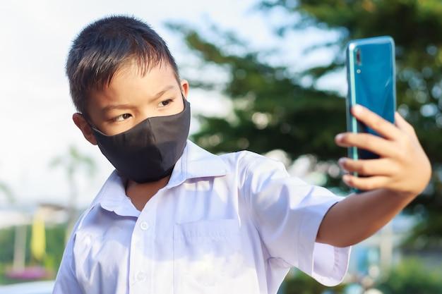 Ragazzo bambino asiatico che indossa una maschera in tessuto nero sul viso per prevenire la malattia di covid-19