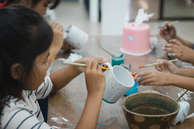 Una bambina asiatica e gli amici si stanno concentrando per dipingere su vetro ceramico con colori ad olio insieme al divertimento. classe di attività creative di arti e mestieri per bambini a scuola. Foto Premium