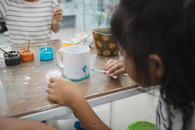 Una bambina asiatica e gli amici si stanno concentrando per dipingere su vetro ceramico con colori ad olio insieme al divertimento. classe di attività creative di arti e mestieri per bambini a scuola.