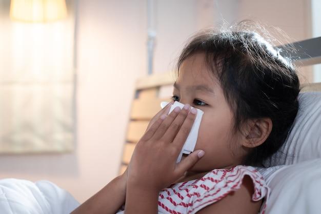 La ragazza asiatica del bambino si ammala, tossisce e starnutisce.
