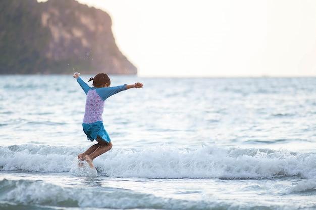 Ragazza asiatica del bambino che salta sulla spiaggia