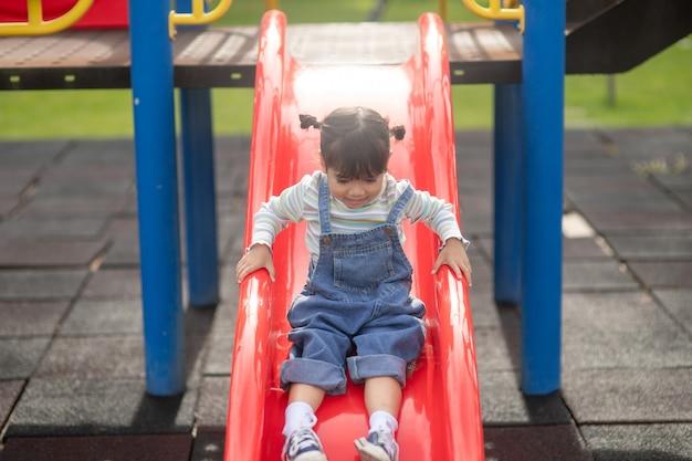 Ragazza asiatica del bambino che gioca nel parco giochi all'aperto. i bambini giocano a scuola o nel cortile dell'asilo. attività estive salutari per bambini.