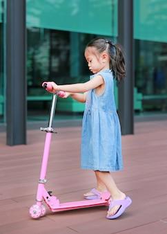Ragazza asiatica del bambino che gioca motorino
