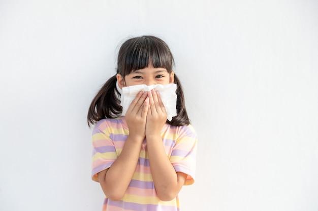 Bambina asiatica malata di starnuti sul naso e tosse fredda su carta velina perché debole o virus e batteri dovuti alla polvere e all'asilo e all'asilo