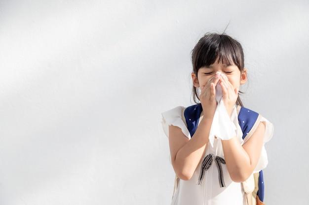 Bambina asiatica malata di starnuti sul naso e tosse fredda su carta velina perché debole