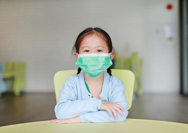 Ragazza asiatica del bambino che indossa una maschera protettiva che si siede sulla sedia del bambino nella stanza di bambini.