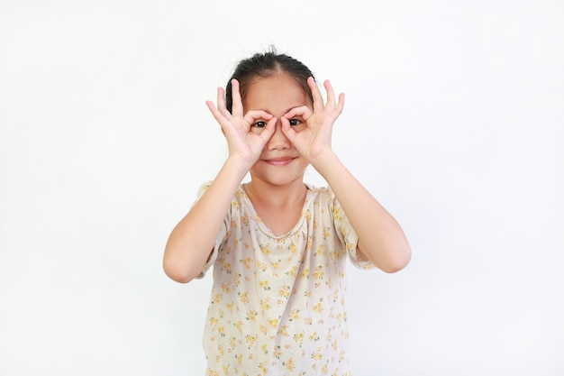 Bambino asiatico che osserva tramite il binocolo immaginario su bianco