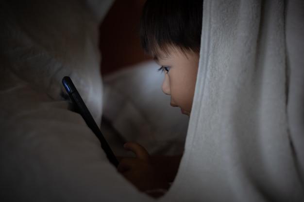 Bambino asiatico che si trova sul letto e che gioca sul telefono cellulare