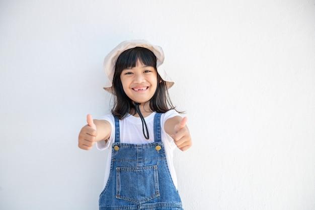 La bambina asiatica mostra i suoi pollici per rallegrarsi felicemente