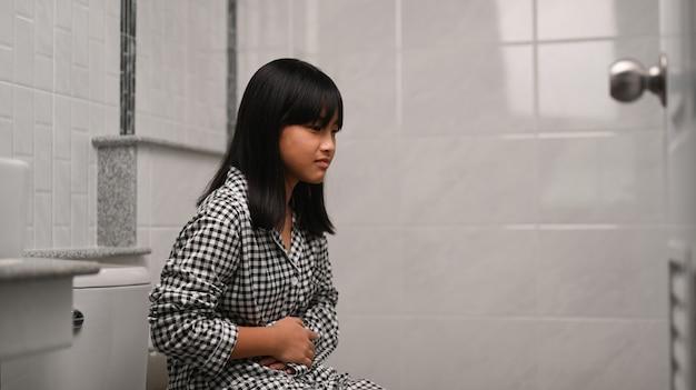 Bambino asiatico seduto in bagno a casa e che soffre di mal di stomaco.