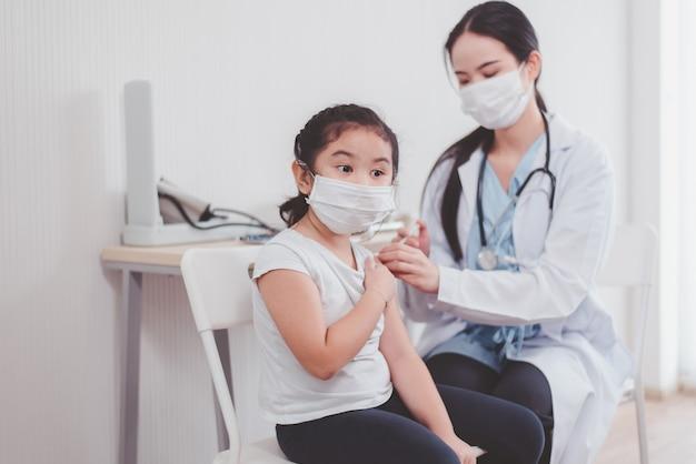 Bambino asiatico che indossa una maschera facciale che viene vaccinato durante la pandemia di coronavirus o covid-19 in ospedale, concetto di vaccinazione