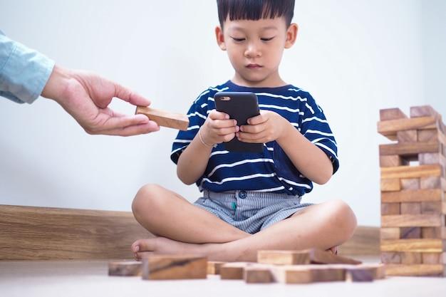 Bambini asiatici nell'età dei social network che si concentrano su telefoni o tablet. non preoccuparti dell'ambiente circostante e hai problemi agli occhi. concetto dei bambini dipendenti del videogioco