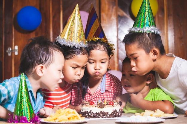 Ragazze e ragazzi asiatici dei bambini che celebrano insieme il compleanno e che soffiano le candele sulla torta di compleanno nella festa insieme