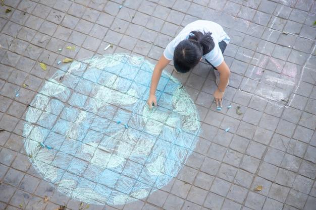 I bambini asiatici giocano all'aperto. la ragazza del bambino disegna un globo del pianeta con una mappa del gesso colorato del mondo sul marciapiede, asfalto. terra, concerto per la giornata della pace.