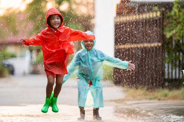 I bambini asiatici che giocano sotto la pioggia sono felici. stanno saltando