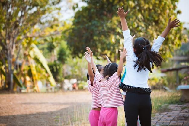I bambini asiatici alzano le mani e giocano insieme con il divertimento nel parco