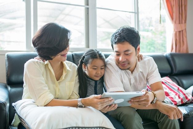 Bambini asiatici che leggono il libro in soggiorno.