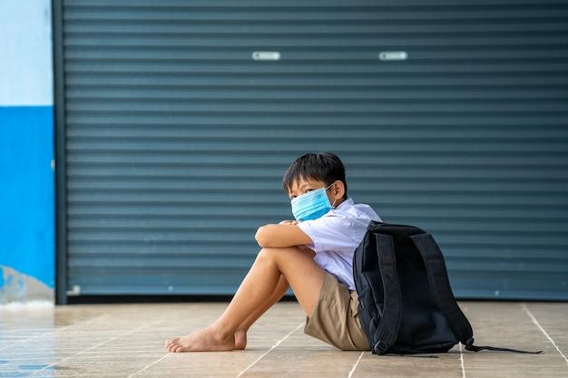 Bambini asiatici in uniforme scolastica che indossa una maschera protettiva per proteggersi dal covid-19, torna a scuola per un nuovo normale concetto di stile di vita.