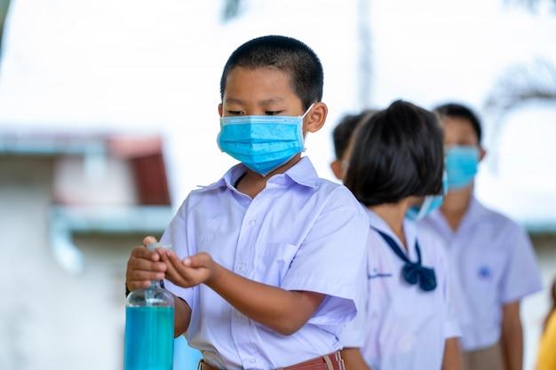 Bambini asiatici in uniforme scolastica che indossa una maschera protettiva per proteggere contro il covid-19, prevenzione contro il covid-19 nella scuola elementare, istruzione, scuola elementare, apprendimento e concetto di persone.