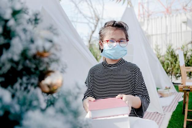 Bambini asiatici che indossano la maschera di protezione che tiene il libro di scuola