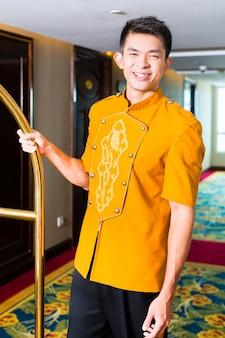 Portiere cinese asiatico o fattorino o paggio che porta la valigia degli ospiti con un furgone nella camera d'albergo