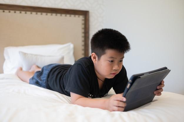 Ragazzo cinese asiatico che gioca a smartphone, bambino usa il telefono e gioca, gioco dipendente e cartone animato