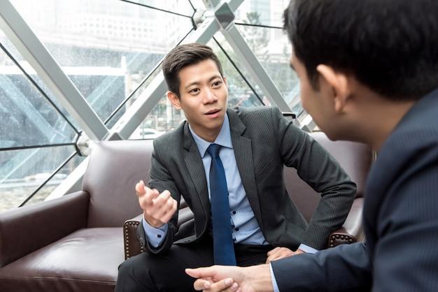 Uomo d'affari cinese asiatico che parla con il suo partner