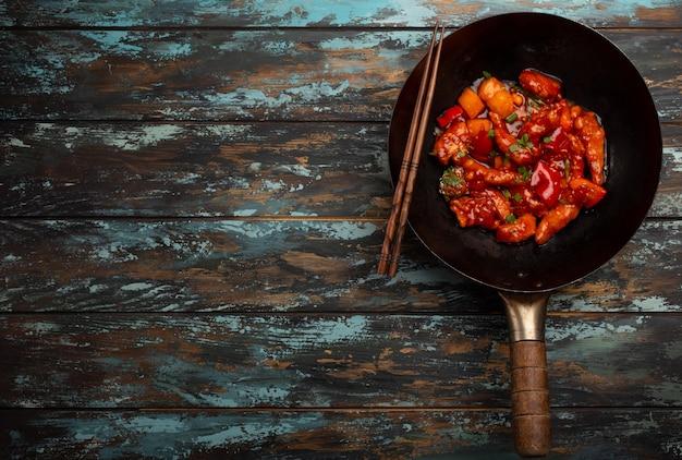 Delizioso pollo in stile asiatico o cinese in salsa agrodolce servito in una padella wok rustica nera su sfondo di legno colorato. concetto di cena asiatica, vista dall'alto, primo piano con spazio per il testo