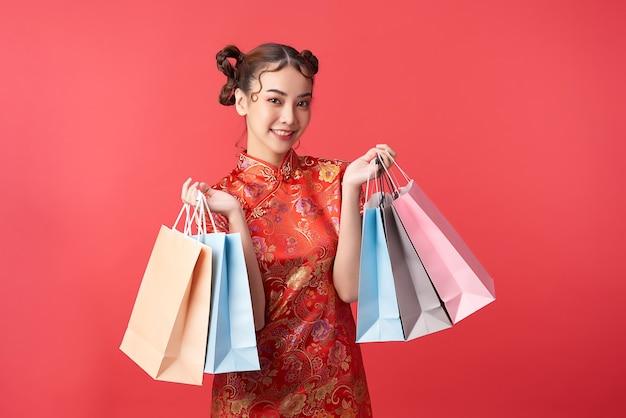 Donna cinese asiatica in vestito tradizionale con le borse della spesa. festival del capodanno cinese.
