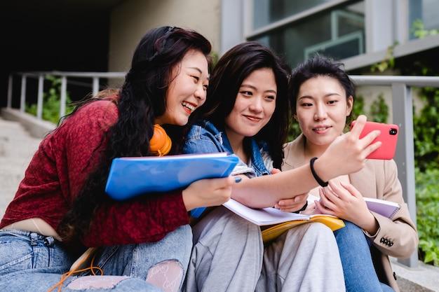 Studenti universitari asiatici che prendono un selfie con un telefono cellulare