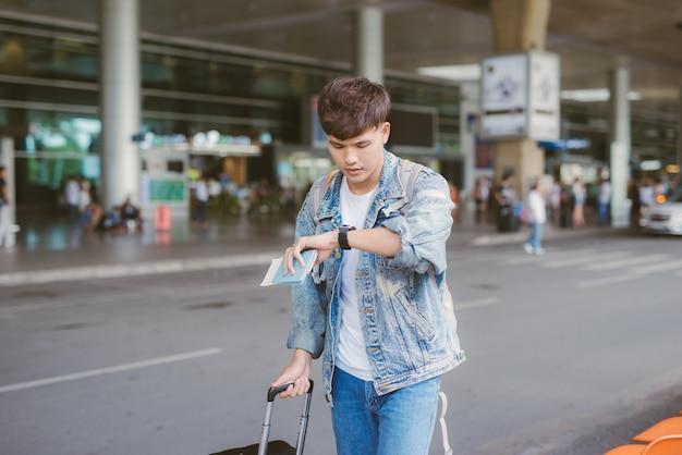 Il turista maschio asiatico confuso guarda il suo orologio all'aeroporto