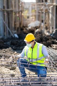Operaio edile asiatico sul cantiere. fabbricazione di barre di rinforzo in acciaio. indossare una maschera chirurgica durante il coronavirus e l'epidemia di influenza