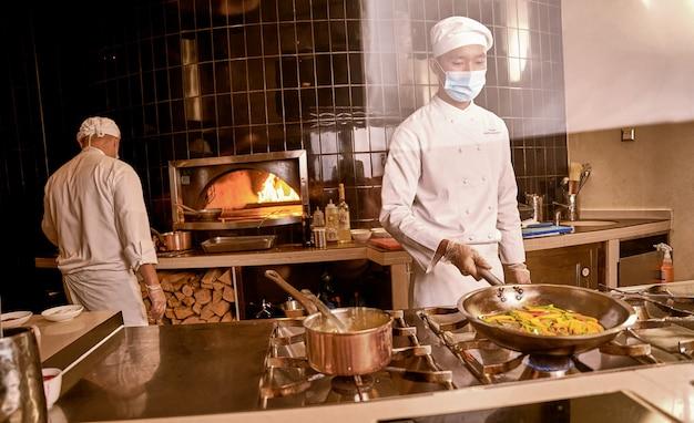 Cuoco asiatico che tiene i peperoni in padella sul fornello