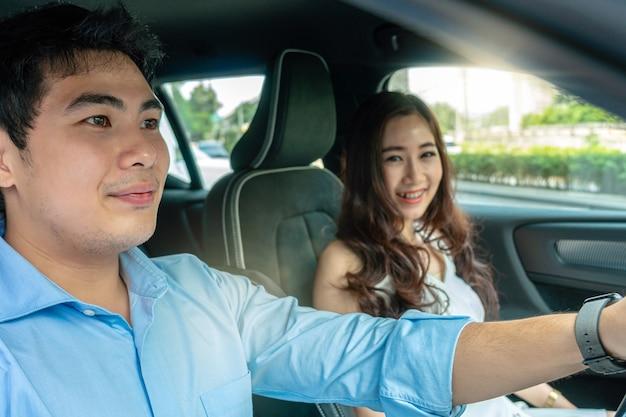 La coppia asiatica sta guidando in un'auto per un test drive prima di acquistare una nuova auto