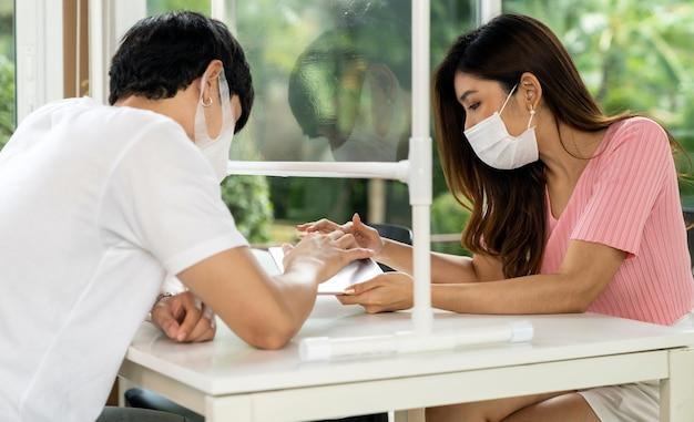 Clienti asiatici delle coppie che cercano menu dalla compressa digitale