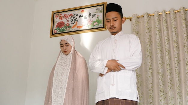 Coppia asiatica che adora insieme a casa