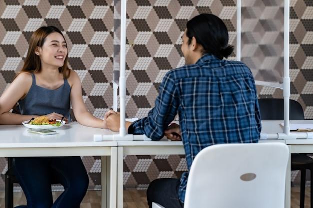 Coppie asiatiche che mangiano fuori al nuovo ristorante normale