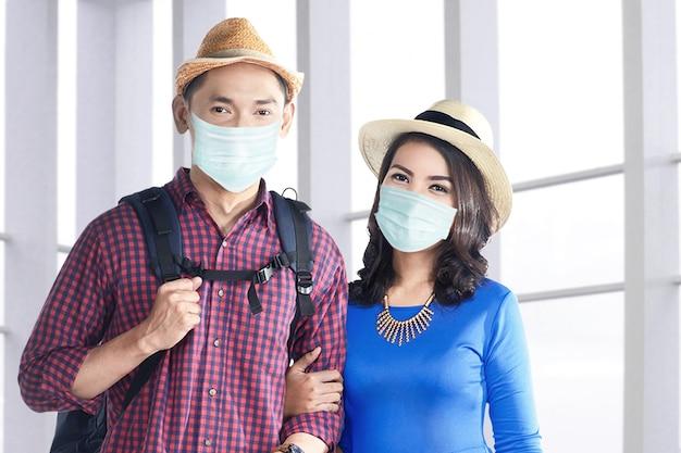 Coppia asiatica nella maschera facciale con borsa valigia e zaino in piedi sul terminal dell'aeroporto. viaggiare nella nuova normalità