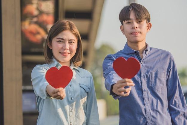 Coppie asiatiche che tengono cuore rosso, persone felici amore dolce san valentino, assicurazione sanitaria, dando amore insieme