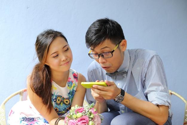 Coppie asiatiche che giocano smart phone in giardino.