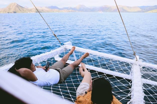 Coppia asiatica che si rilassa sulla rete del catamarano mentre usa lo smartphone con vista sul mare e colline