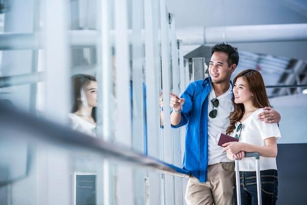 Viaggiatore asiatico delle coppie che tiene il passaporto all'aeroporto